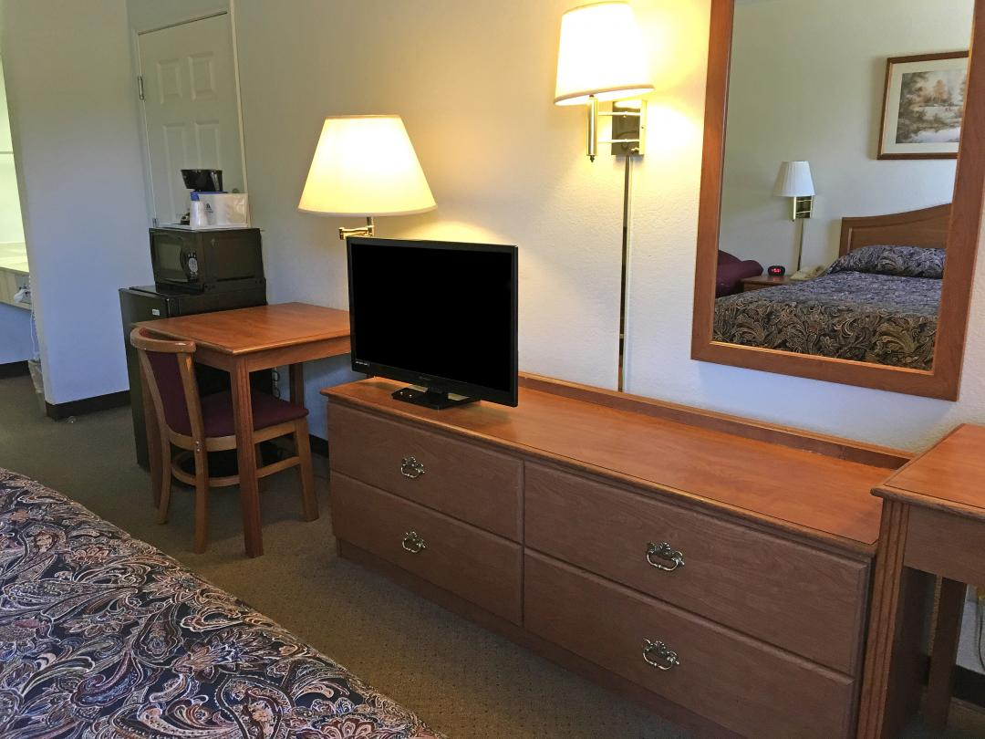 Guest room with one queen bed, desk, chair, fridge and microwave