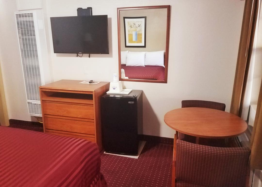 Guestroom amenities of mini-fridge, table with chairs, TV
