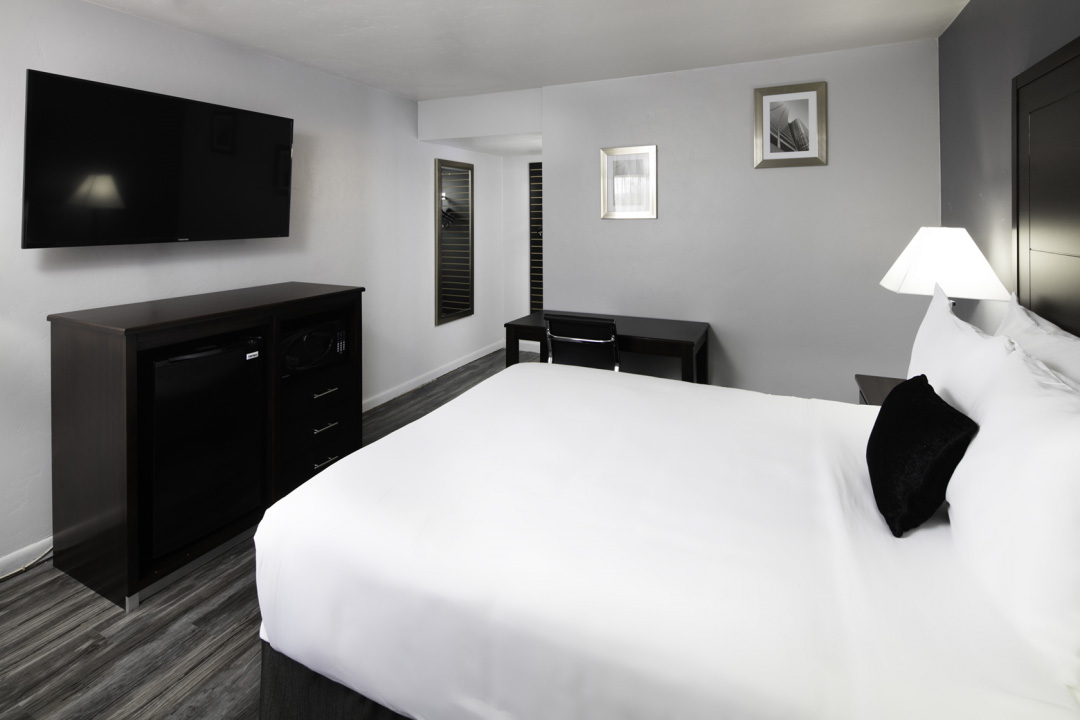 Spacious King guest room with desk and flatscreen TV