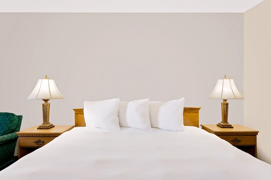 queen bed with three pillows and white linens
