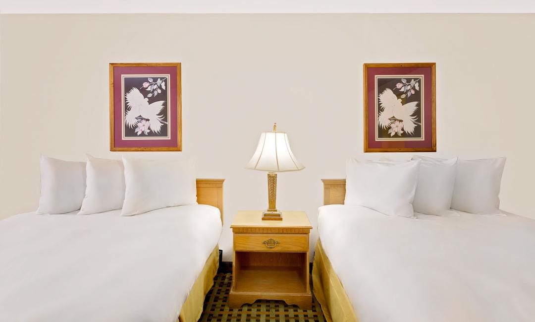 Guest room with two queen beds and white linens
