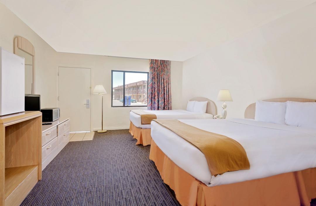 Spacious guest room with two queen beds, fridge and microwave