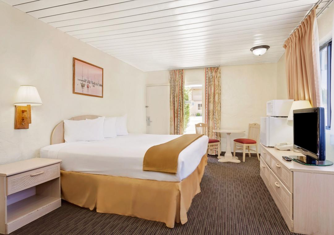 Spacious guest room with king bed, table and chairs