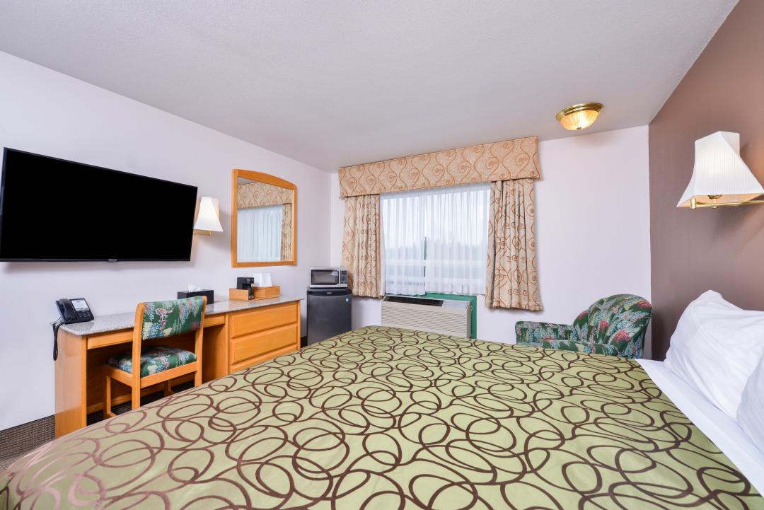 One king bed with desk, flat screen TV, microwave and fridge