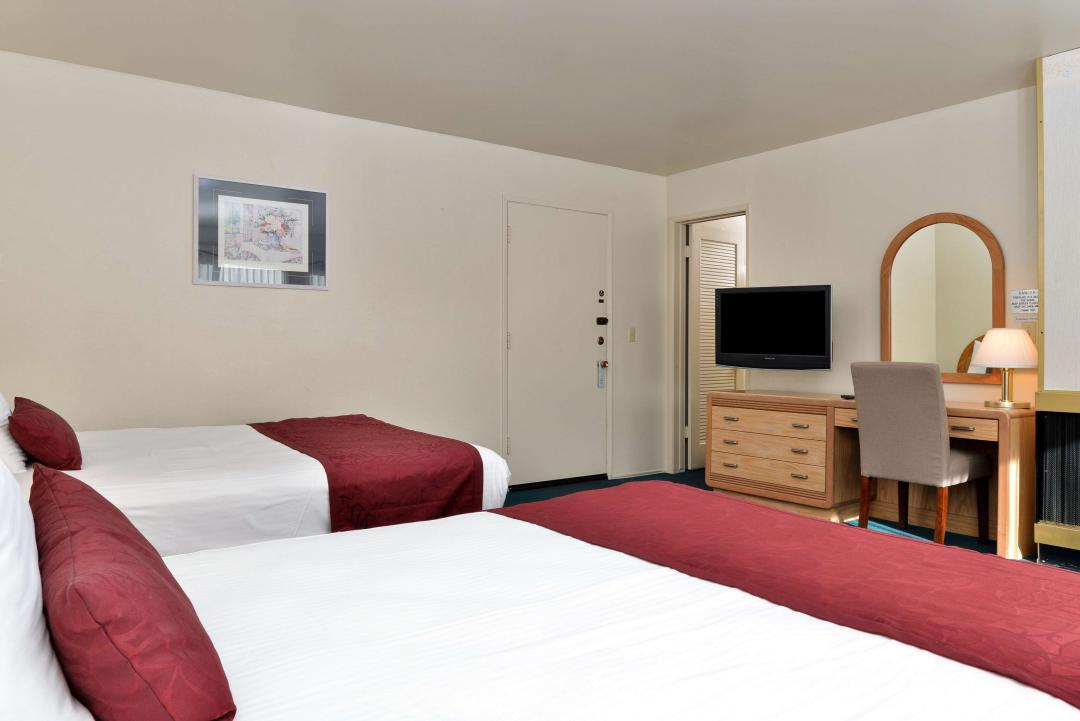 A view of our spacious Two Double Beds guest room with a TV and a Desk with Lamp.