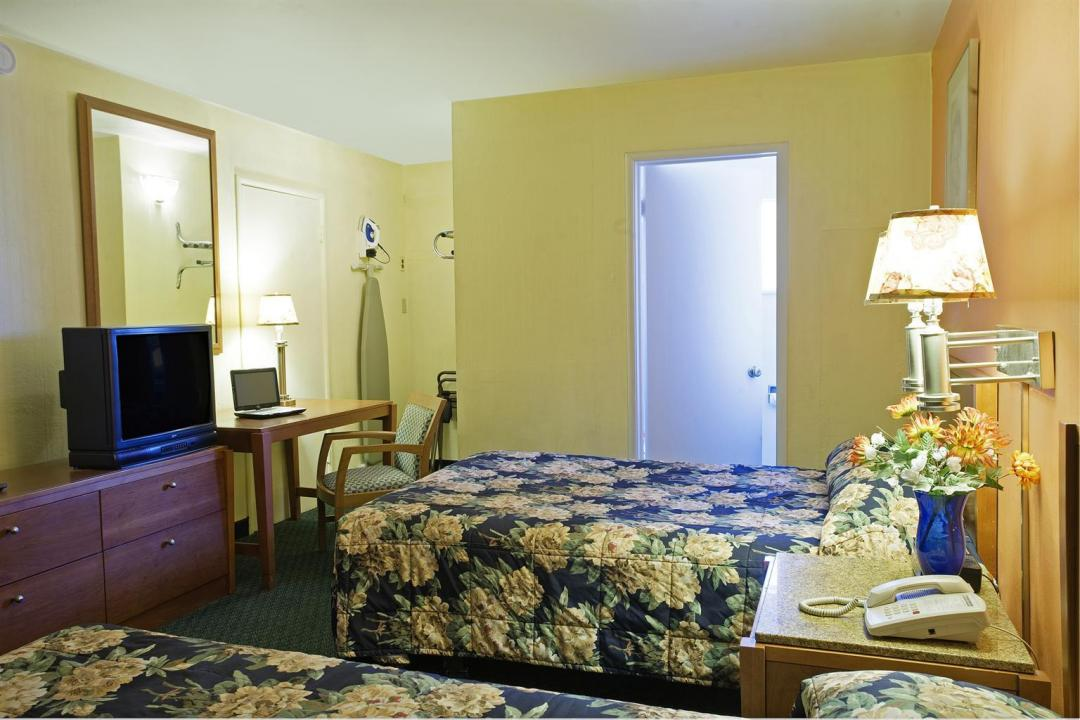Guest room with two double beds, desk, and chair