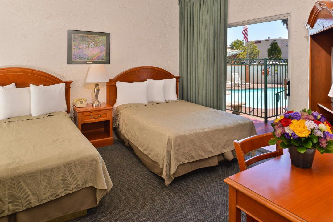 Two double beds guestroom with night stand, patio with pool view