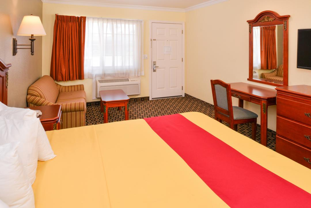 Guest room with one king bed, desk, sofa and table