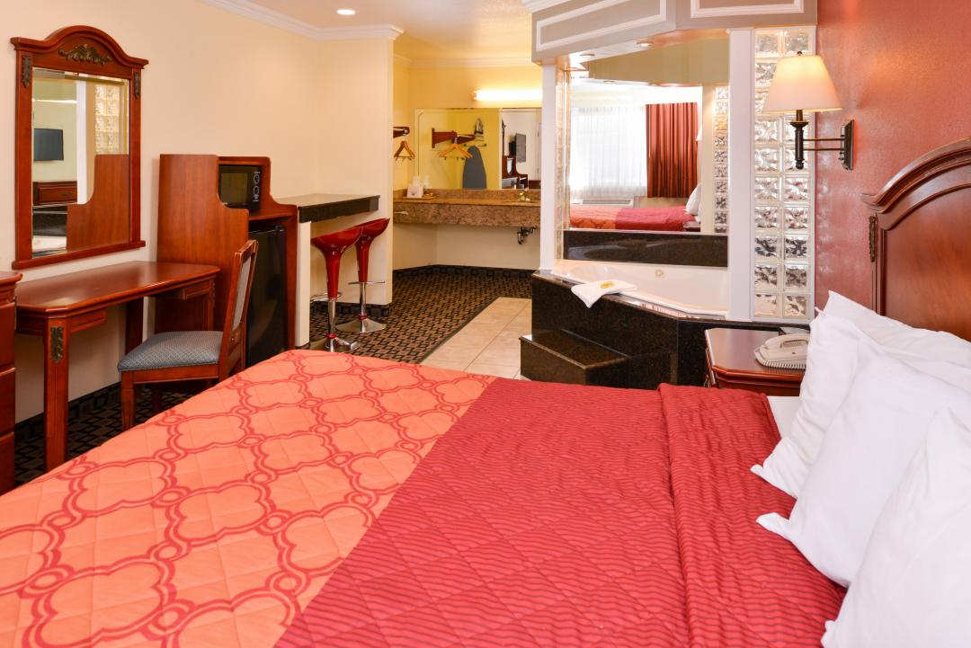Guest room with one bed, desk, chair, fridge, microwave and jacuzzi tub