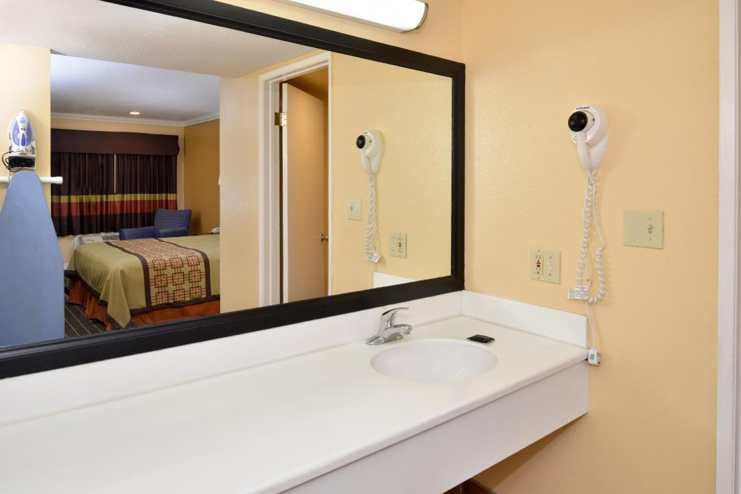 Clean, well lit guest room bathroom sink and blowdryer