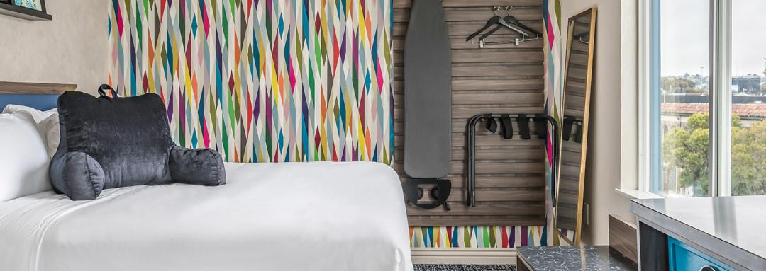 Guest room with queen bed, ironing board, andartistically designed wall