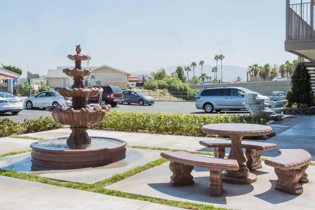 Street view of exterior hotel featuring fountains, seating and parking.