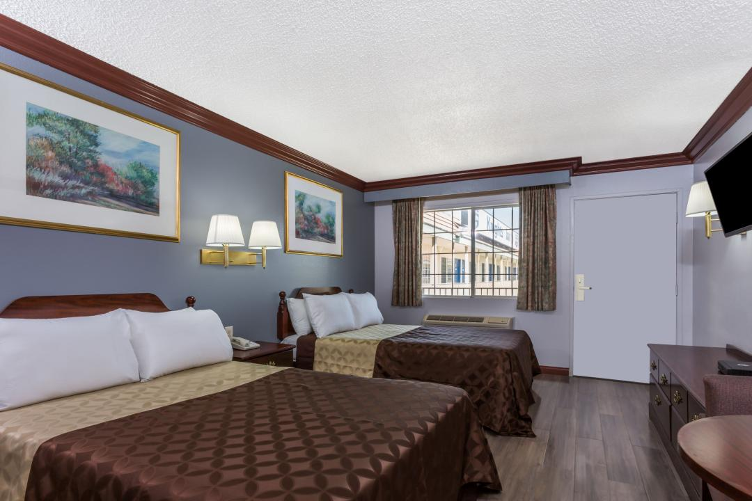 Clean, well lit two double beds guest room, featuring dark wood flooring, table and TV.