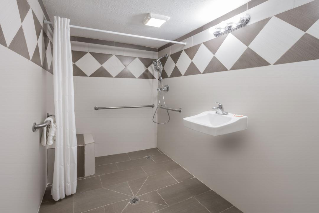 Spacious, clean, well lit accessible shower with seating and grab bars.