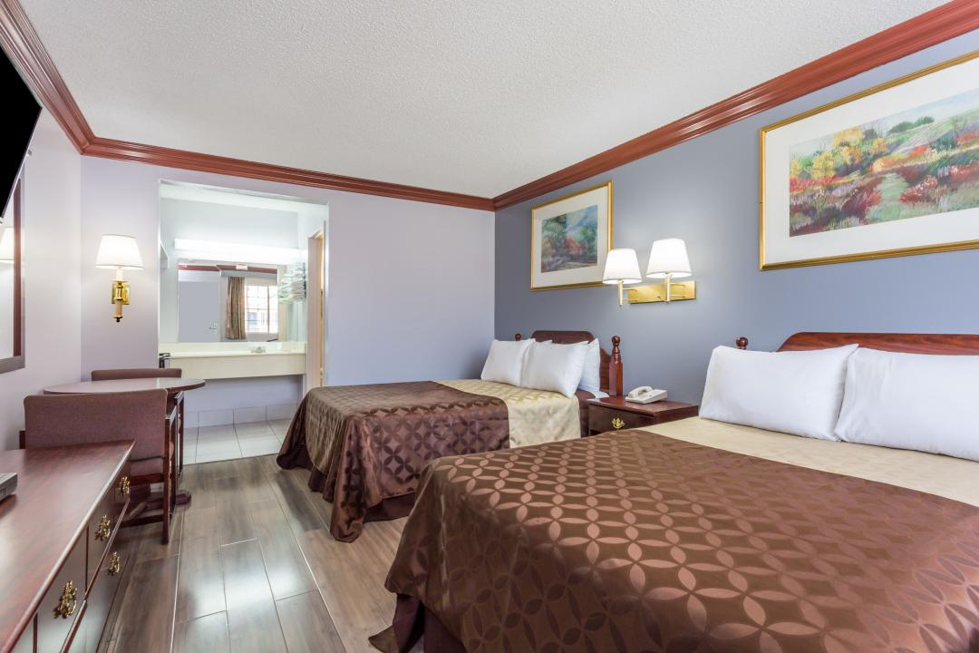 Well lit two double beds guest room, featurng dark wood flooring, table, chairs and TV.