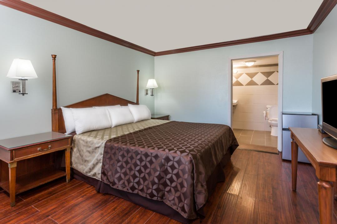 Well lit accessible king guest room featuring dark wood flooring, with refrigerator, and TV.