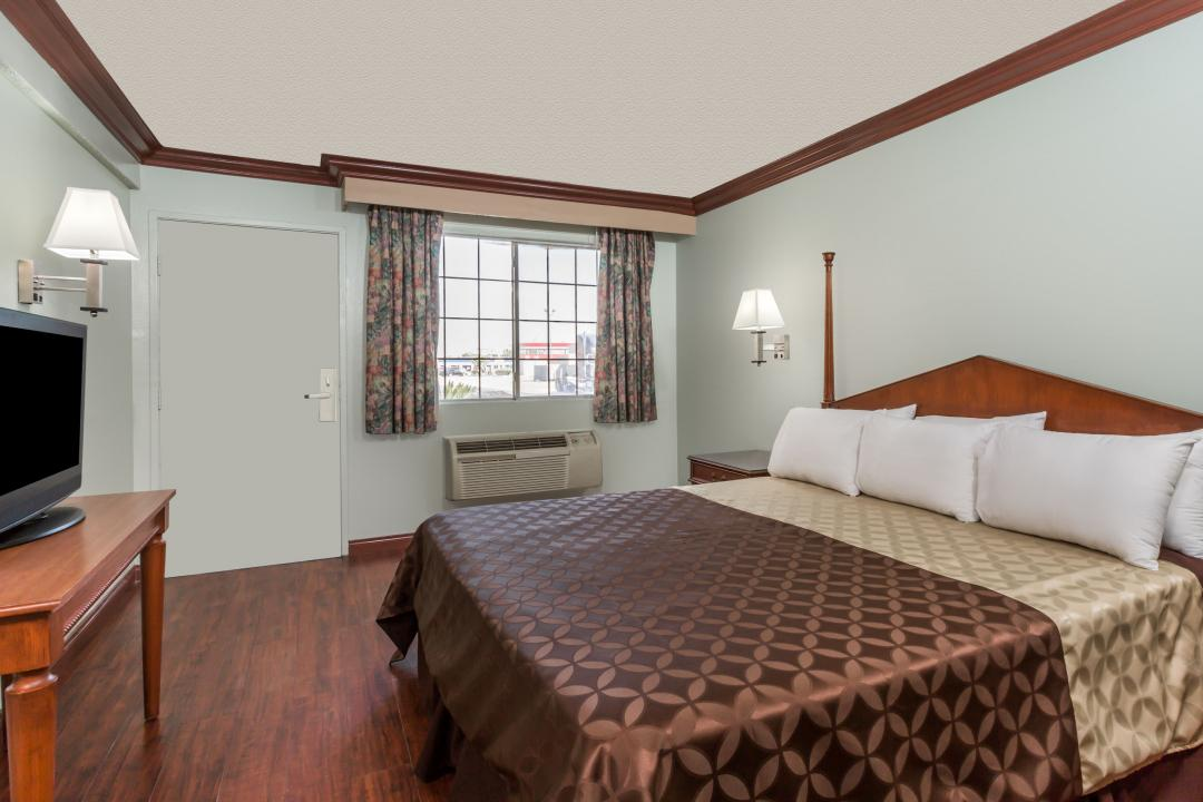 King guest room featuring dark wood flooring, with TV.