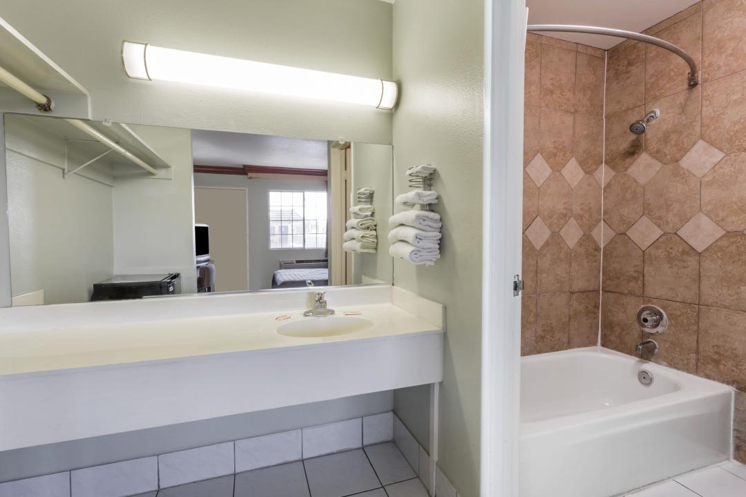 Clean, bright, modern guest bathroom with tub.