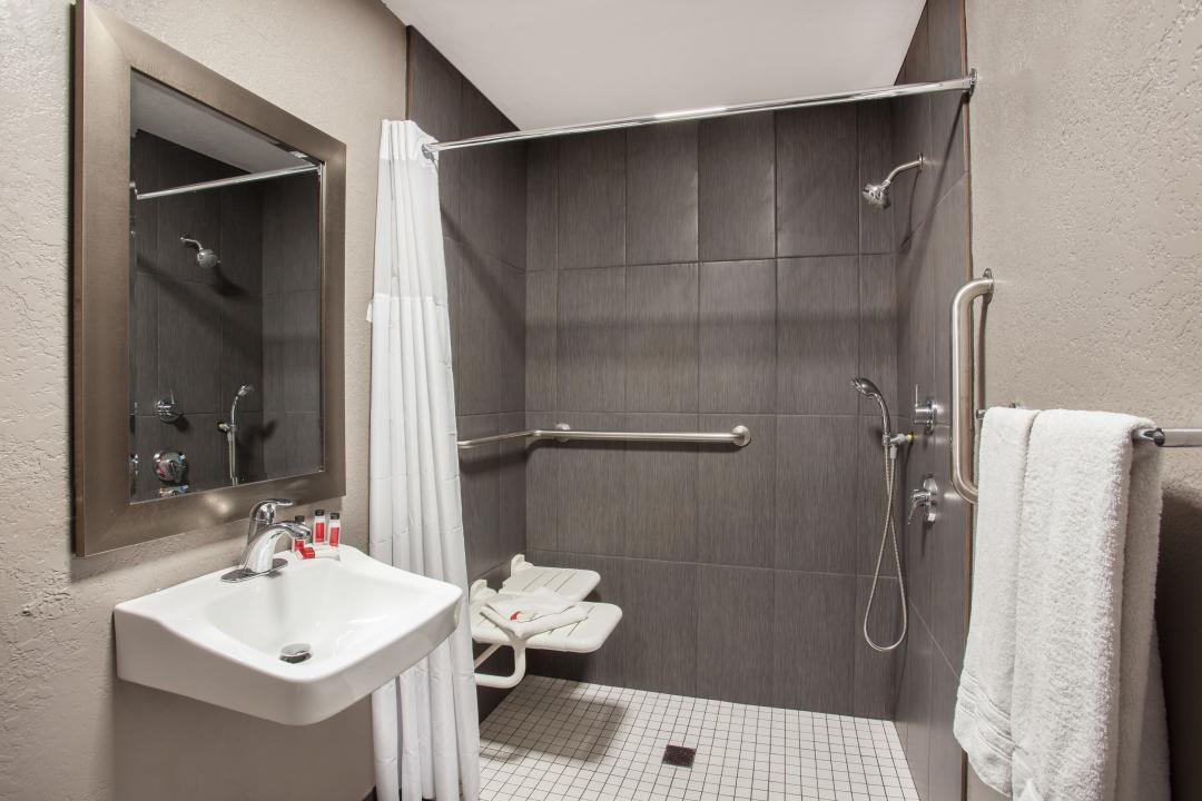Accessible bathroom with roll-in shower, shower bench and handrails