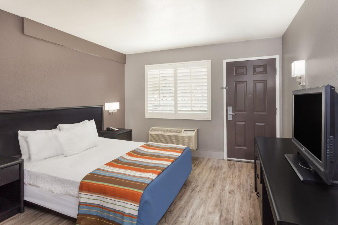Guestroom with one queen bed, white sheets, flatscreen TV, air conditioning and egress to outdoors