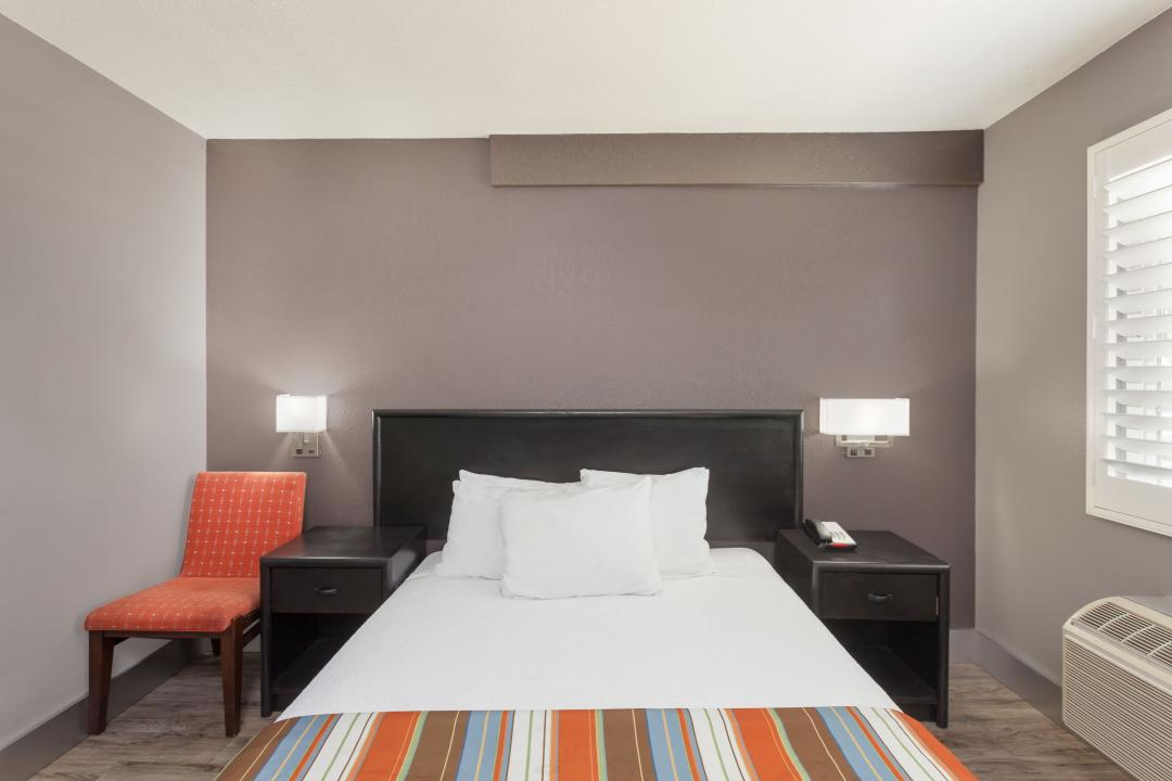Guestroom with one queen bed, white sheets, air conditioning and chair