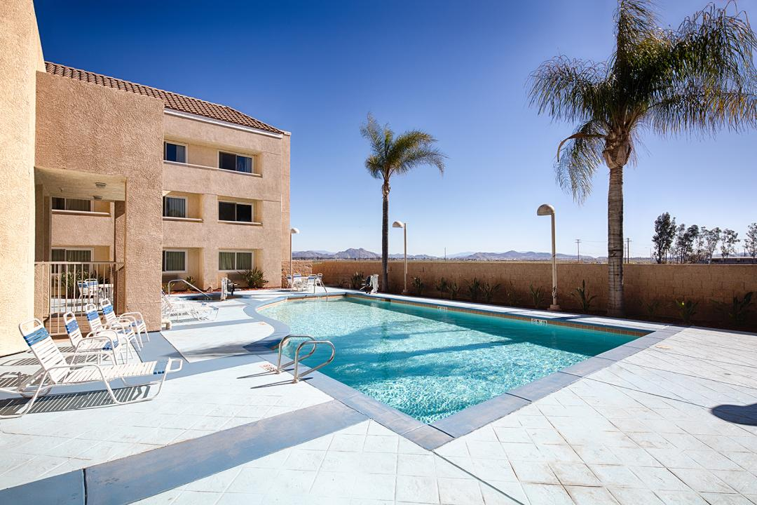Outdoor pool area with palm trees, lounge chairs, mountains in background