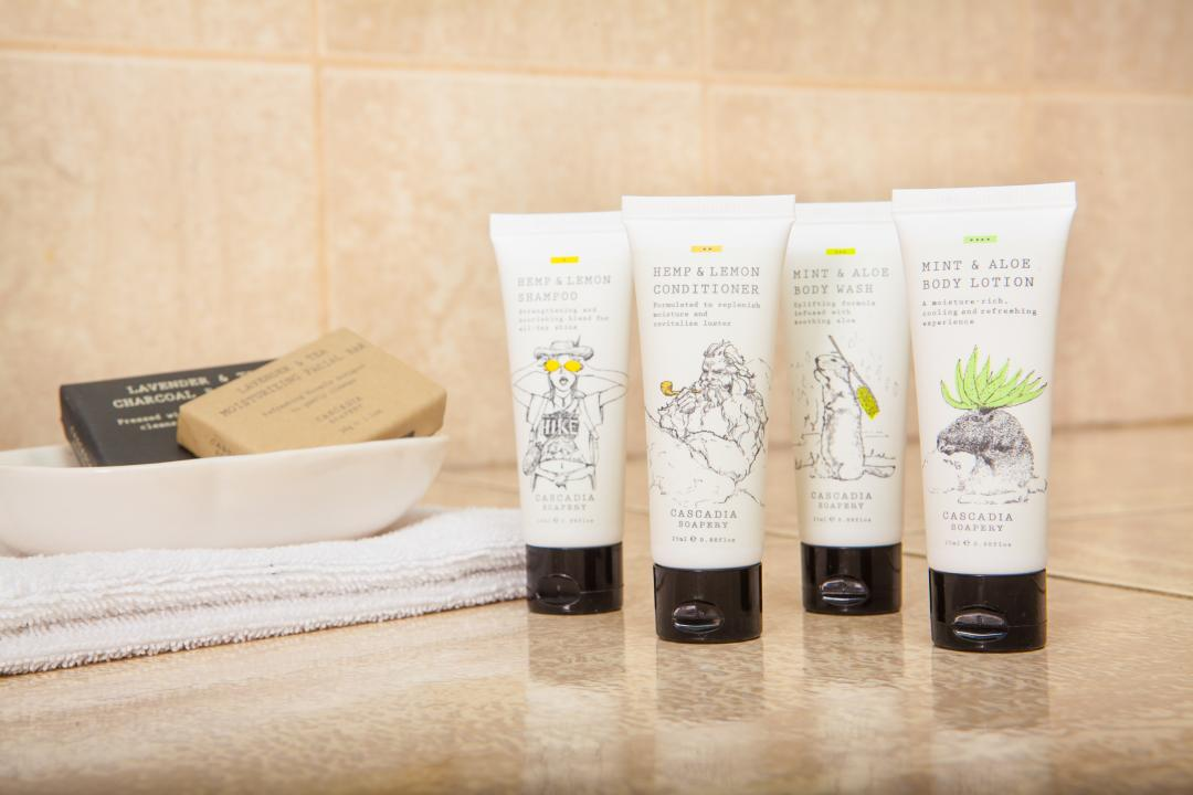 Guest bathroom toiletries with shampoo, conditioner, body wash, lotion, soaps