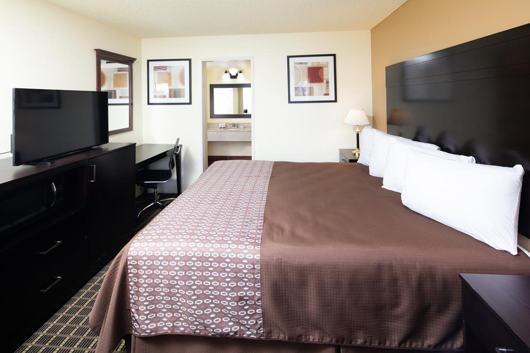 Spacious King guest room with desk, armchairs and flatscreen TV