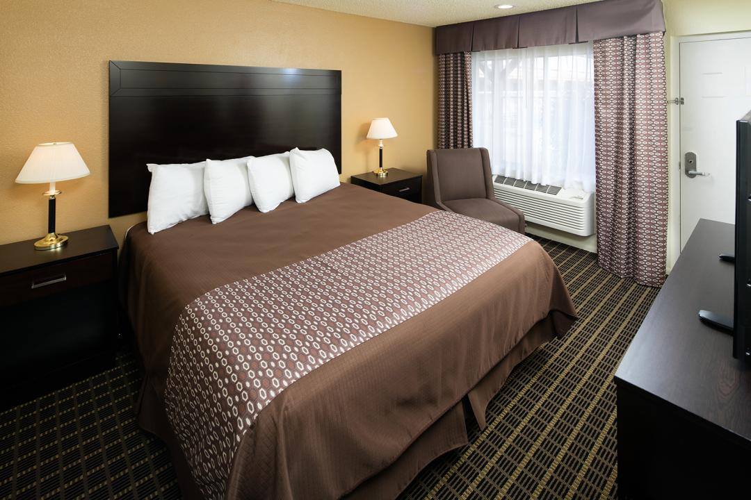 Spacious King guest room with armchairs and flatscreen TV