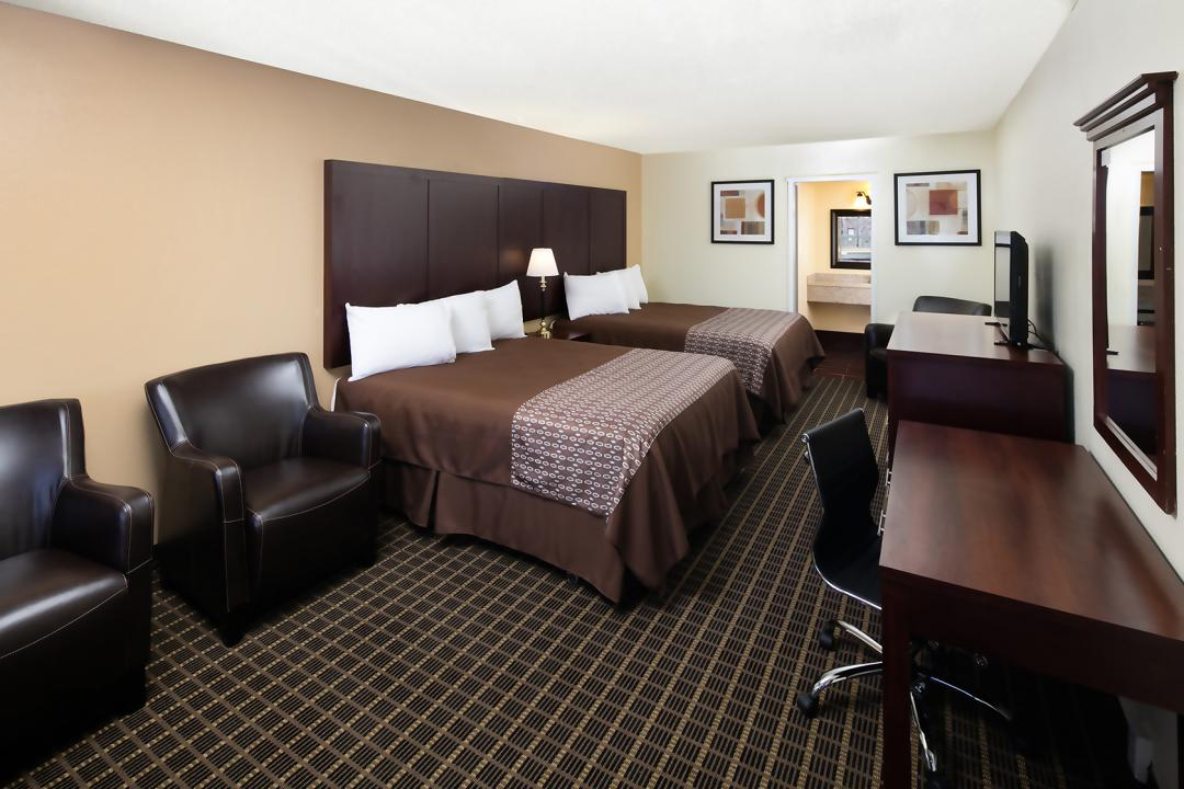 Spacious Two Queen guest room with desk, armchair and flatscreen TV