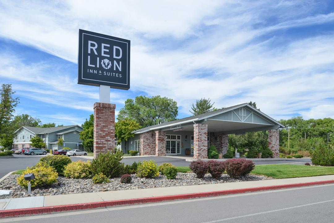 Hotel front exterior from street with driveway and Red Lion Inn & Suites sign