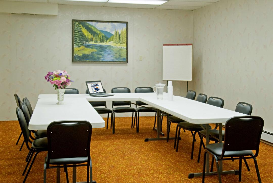 Meeting room with three tables with laptop