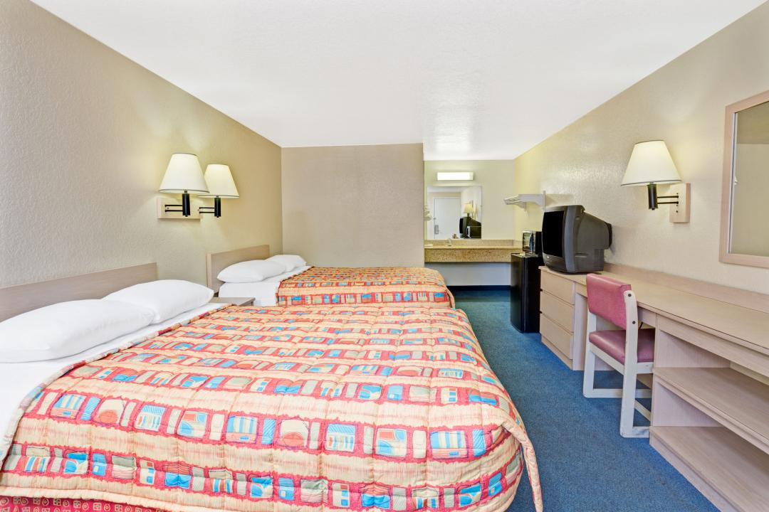 Guest room with two double beds, desk, fridge and microwave