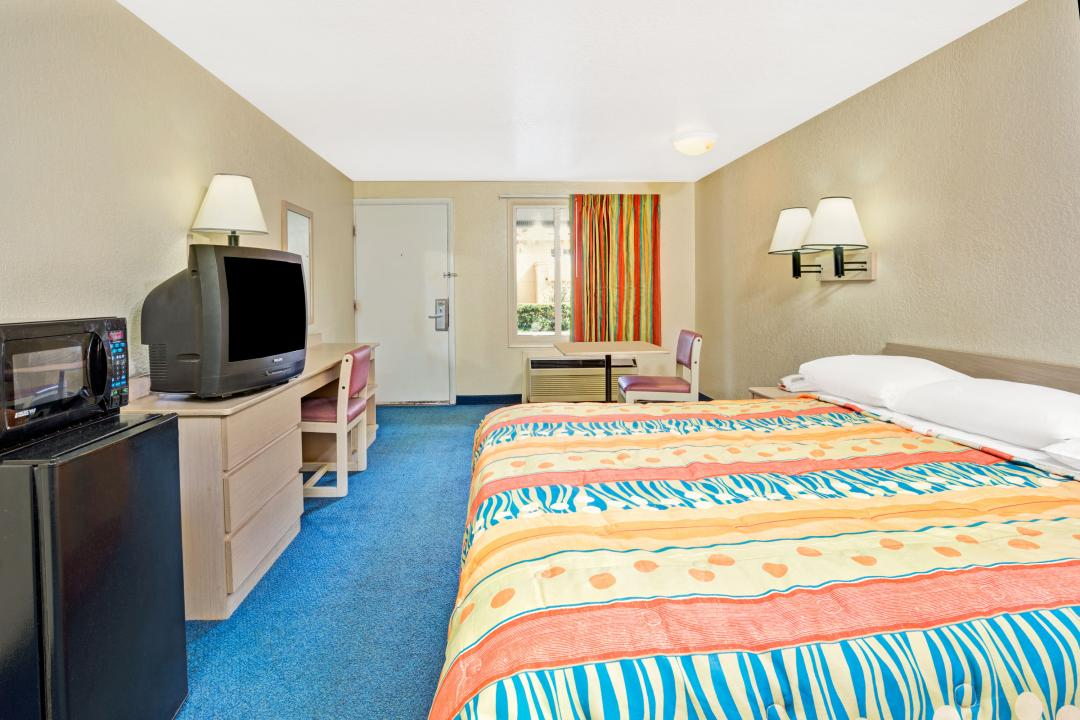 Guest room with one king bed, desk, fridge and microwave