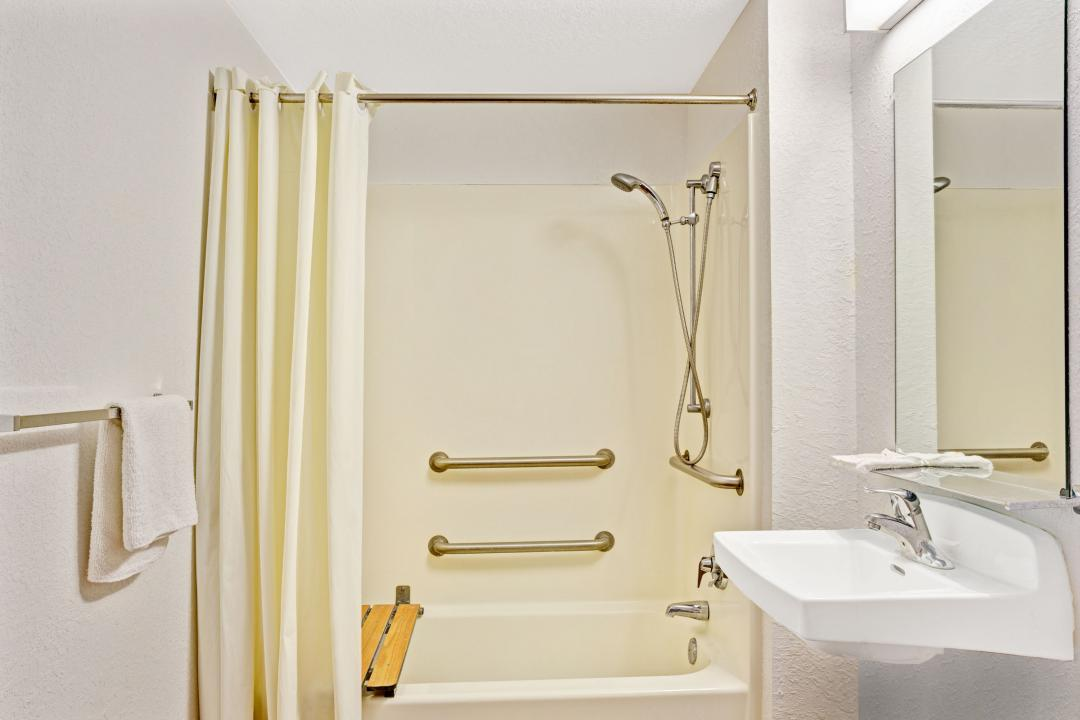 Clean, well lit guest room sink and bathtub with grab bars