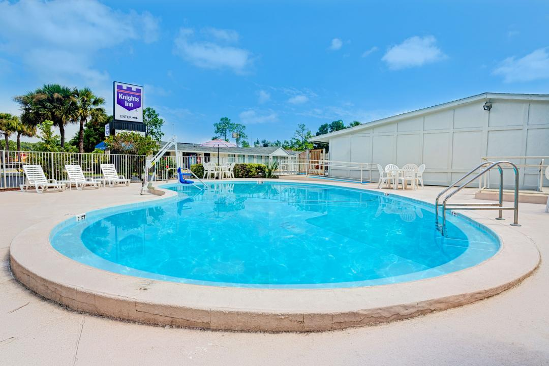 Clearblue, fenced in pool with tables, chairs, lounge chairs and a handicap lift