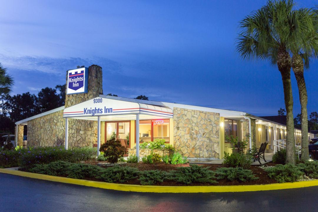 Hotel entrance covered by awning lit at dusk