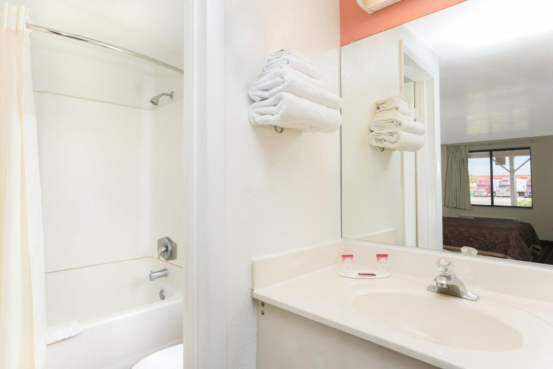 Guest bathroom vanity with shower tub combination and bath amenities