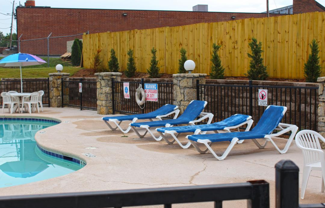 Outdoor pool lounging area with wooden fence