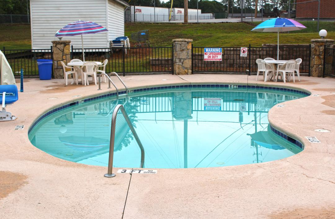 Outdoor pool with white tables and umbrellas