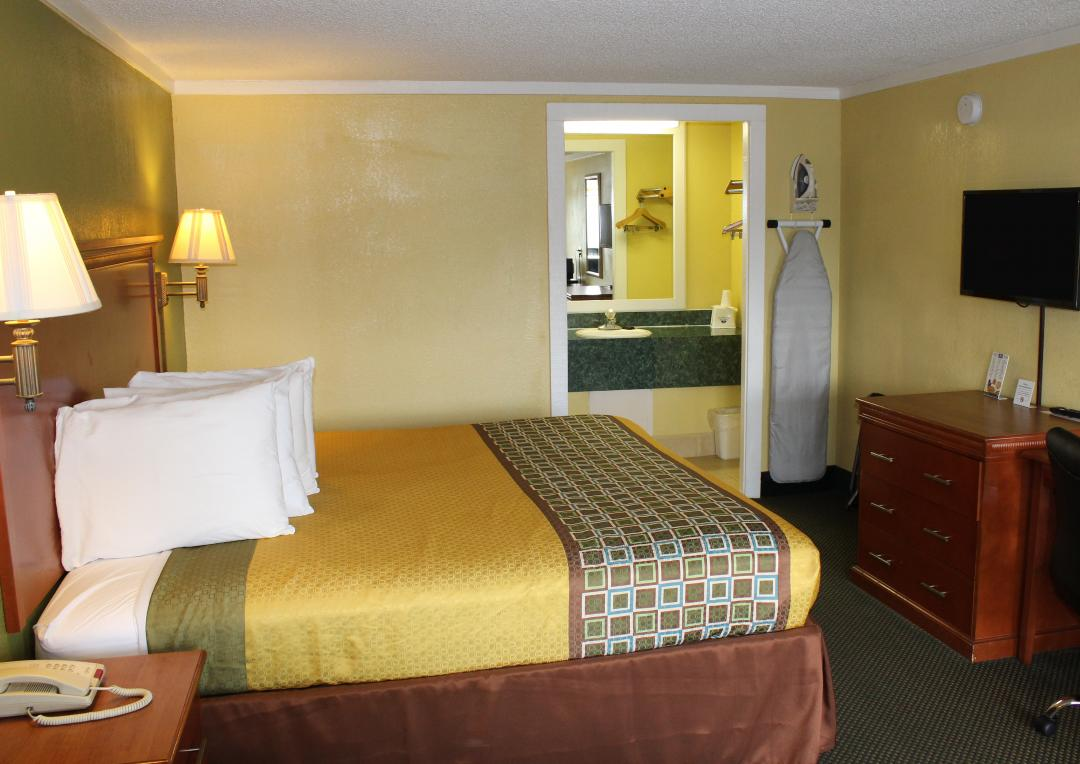 Guest room with one king bed, desk, chair and ironing board