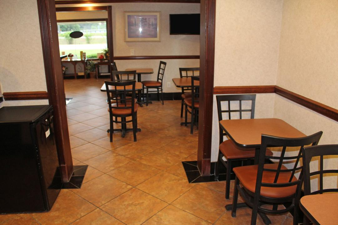 Spacious dining area with ample tables and chairs and small fridge