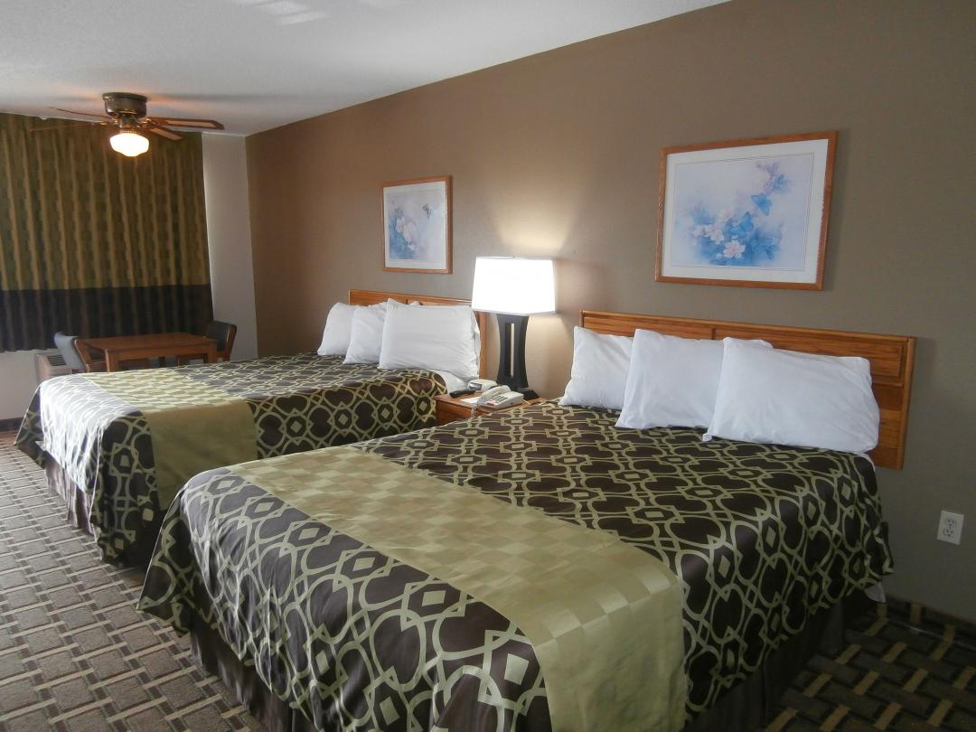 Spacious two queen guestroom with table, chairs and blackout curtain