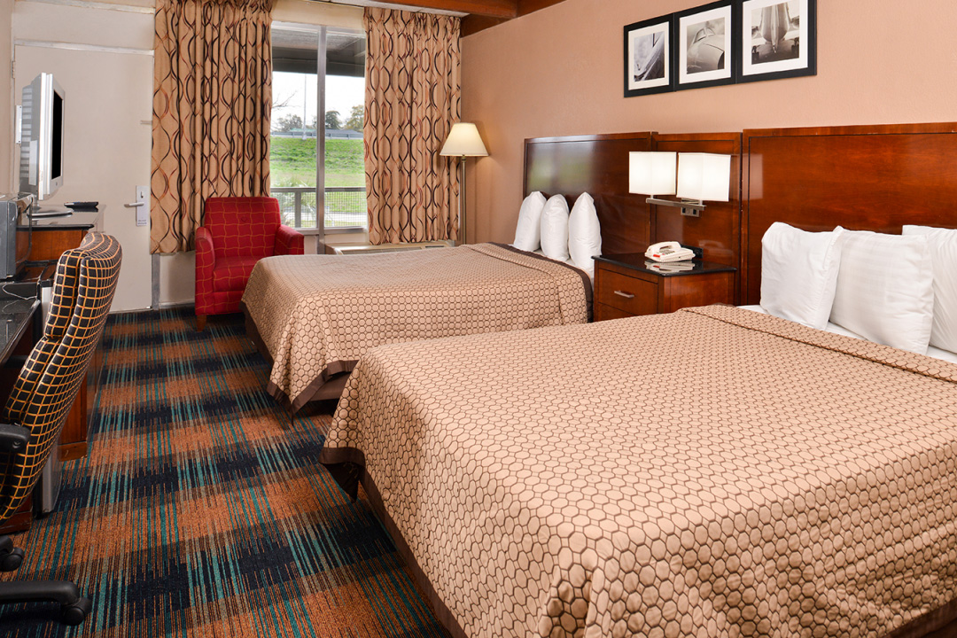 Guest room with two queen beds, sofa chair, desk, and rolling chair