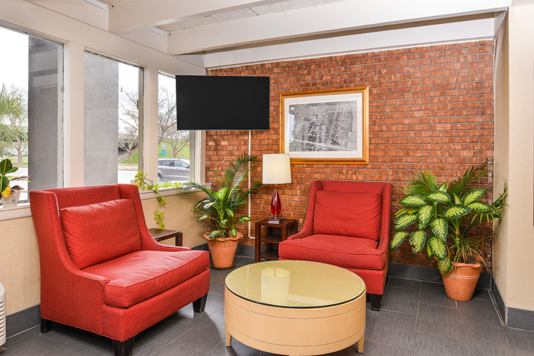 Lobby area with red sofa chairs, coffee table, and tv