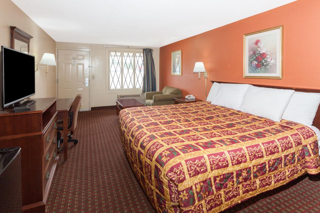 Spacious King guest room with desk, chair, arm chair, flat screen TV, microwave and refrigerator.