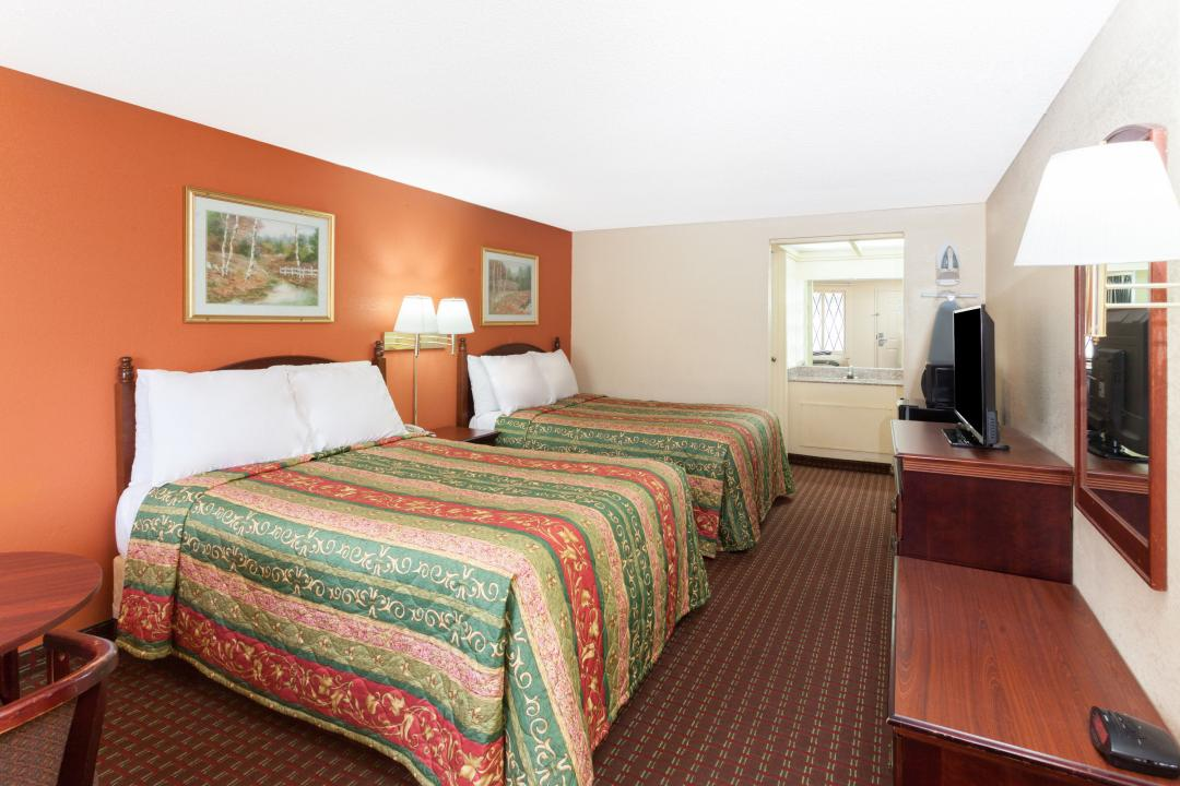 Spacious two Queen guest room with, desk, table, chairs, refrigerator and flat screen TV