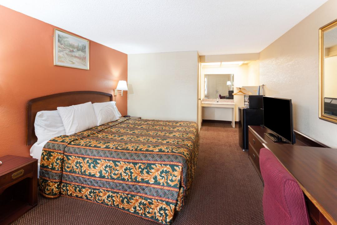 Spacious King guest room with desk, chair, flat screen TV, microwave and refrigerator.