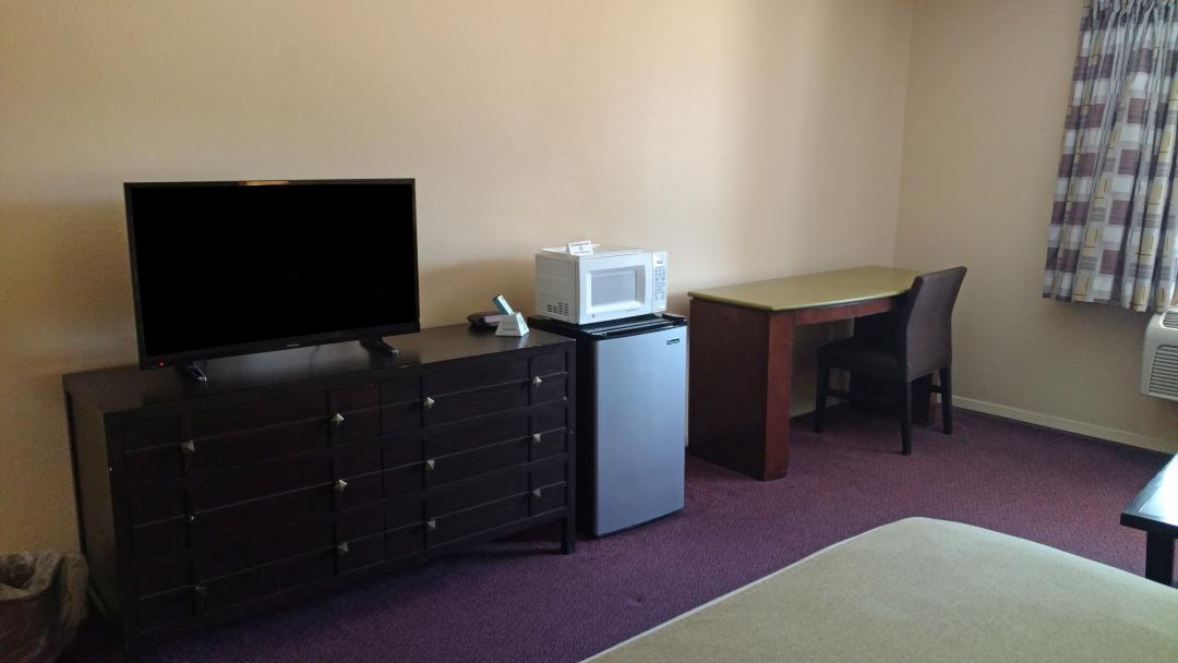 Guest room with desk, chair, fridge and microwave
