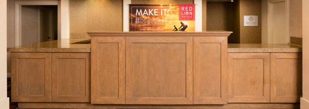 Lobby wooden front desk with hotel signage